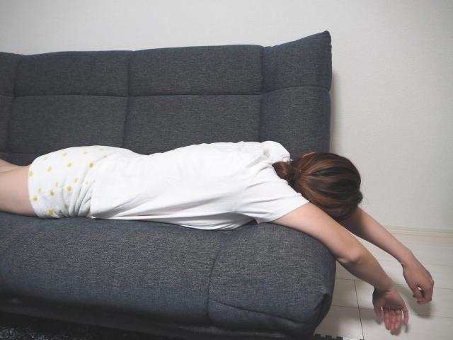 疲れてソファに横たわる女性
