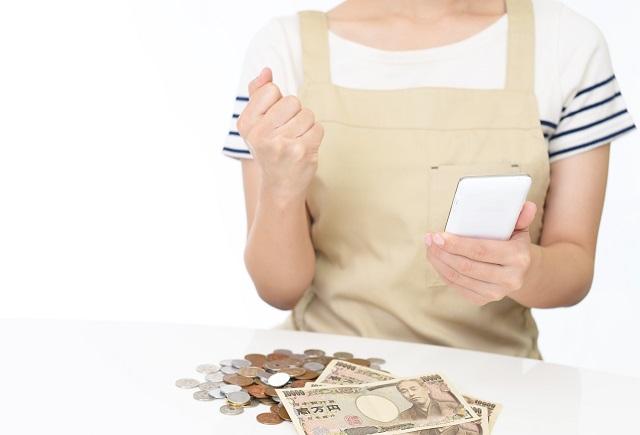 スマホを持つ女性とお金